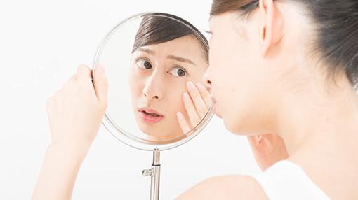 鏡を見て目を気にする女性